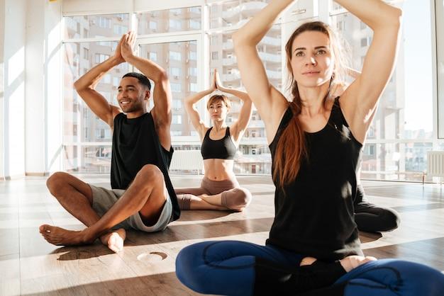 Gruppo di giovani felici che si siedono e che meditano nello studio di yoga di aat di posa del loto