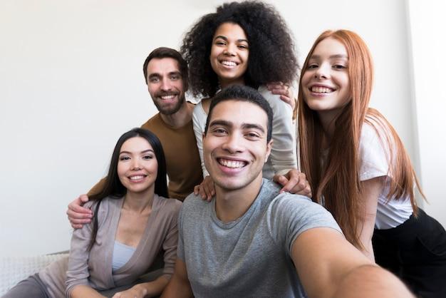 Gruppo di giovani felici che prendono un selfie