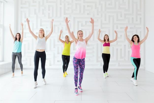 Gruppo di giovani donne felici con allenatore che hanno un allenamento cardio nello studio fitness