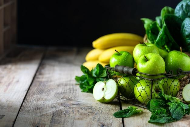 Un gruppo di mele verdi sane, spinaci, banane e menta sono gli ingredienti per un frullato. detox, dieta, concetto di cibo sano e vegetariano. spazio libero per il testo. copia spazio.