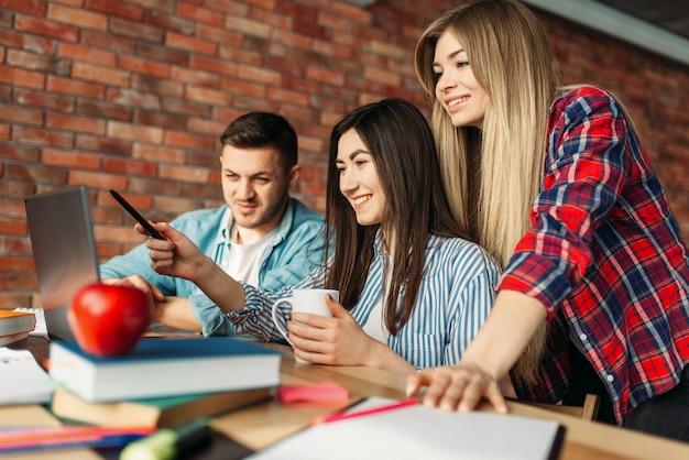 Gruppo di studenti delle scuole superiori che guardano insieme sul computer portatile. persone con informazioni di ricerca su computer in internet, lavoro di squadra, progetto comune