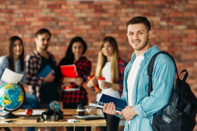 Gruppo di studenti delle scuole superiori con libri di testo in piedi presso il muro di mattoni.