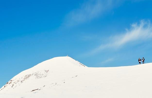 Un gruppo di escursionisti che salgono su una montagna nevosa nella soleggiata mattina d'inverno