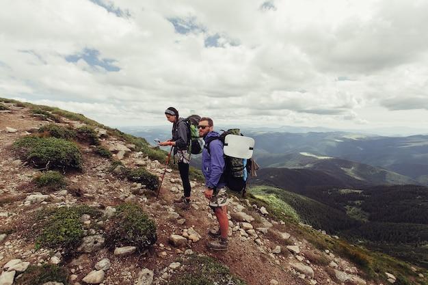 Un gruppo di escursionisti con zaini cammina lungo un sentiero verso un crinale di montagna