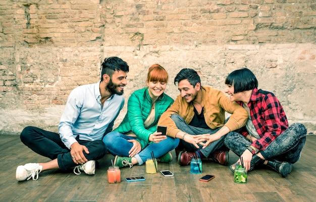 Gruppo di migliori amici hipster con smartphone in posizione alternativa sgangherata