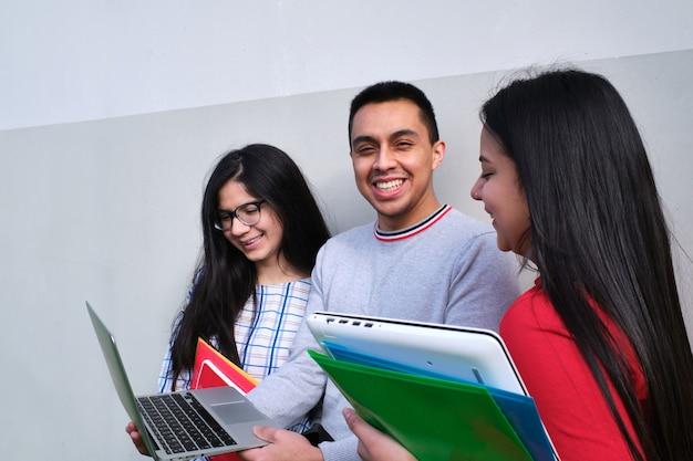 Gruppo di studenti ispanici con un laptop al di fuori dell'università