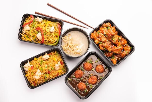Gruppo di cibo indo cinese consegnato a casa in confezioni di plastica, contenitori o scatole contenenti spaghetti schezwan, riso fritto, pollo al peperoncino, manciuria e zuppa.