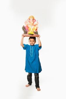 Gruppo di bambini indiani che tengono l'idolo di ganpati sul festival di ganesh o chaturthi, accogliendo dio. in piedi isolato su sfondo bianco