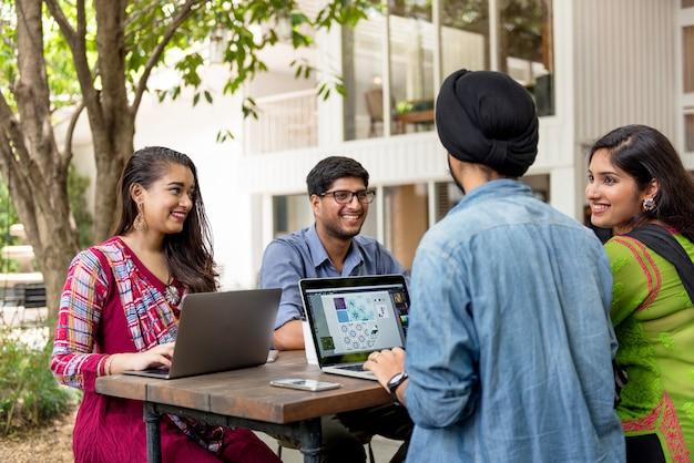 Il gruppo di gente indiana sta usando il computer portatile del computer