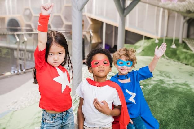 Gruppo di bambini interculturali in abbigliamento di supereroi in piedi davanti alla telecamera durante il gioco nella scuola materna