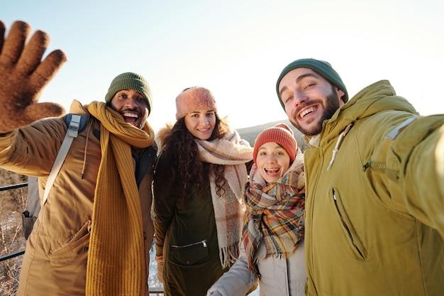 Gruppo di amici interculturali che fanno selfie durante il freddo durante la giornata invernale