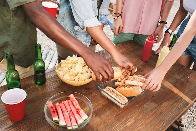Gruppo di amici interculturali che prendono hotdog alla griglia freschi