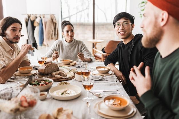 Gruppo di amici internazionali seduti a tavola pieni di cibo che parlano sognante tra loro