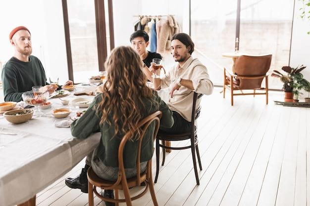 Gruppo di amici internazionali seduti al tavolo pieno di cibo che parlano pensosamente tra loro