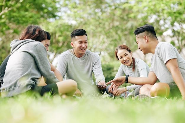Gruppo di giovani studenti gioiosi seduti su un prestito d'erba nel campus e che discutono di un nuovo modello di smartphone o di un'applicazione mobile