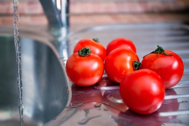 Un gruppo di succosi pomodori rossi freschi in coda per un lavaggio. lavare frutta e verdura prima di mangiare. cura della salute e dell'igiene.
