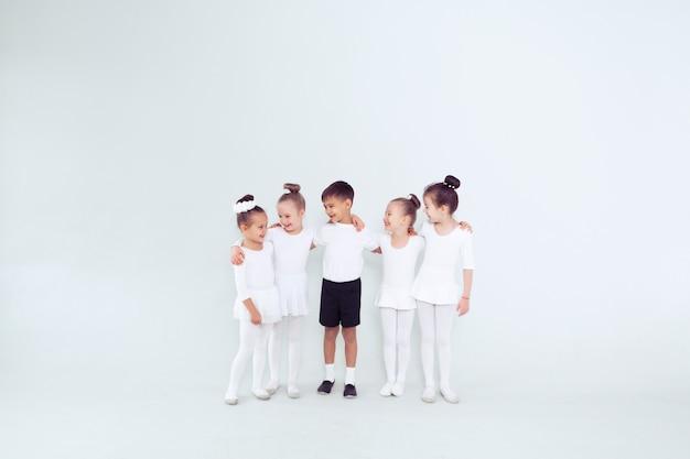 Gruppo di ragazzi e ragazze che ballano in una classe bianca o in uno studio che sorridono e si abbracciano insieme