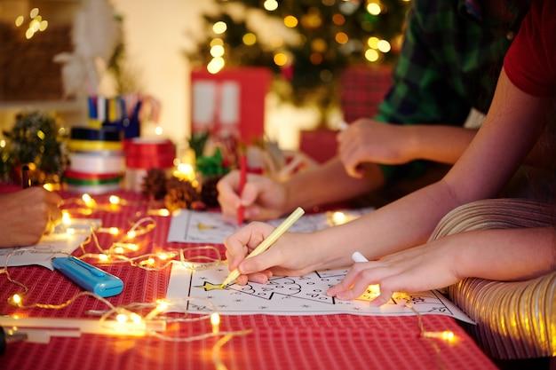 Gruppo di bambini che dipingono immagini di natale da colorare per decorare la stanza per la festa