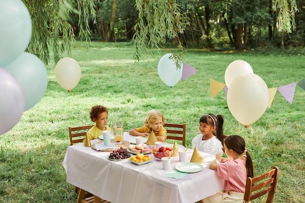 Gruppo di bambini al tavolo da picnic all'aperto decorato con palloncini per la festa di compleanno nello spazio estivo della copia