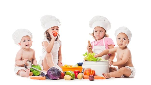 Un gruppo di bambini gioca e cucina con le verdure. piccoli chef isolati su bianco, concetto di alimentazione sana