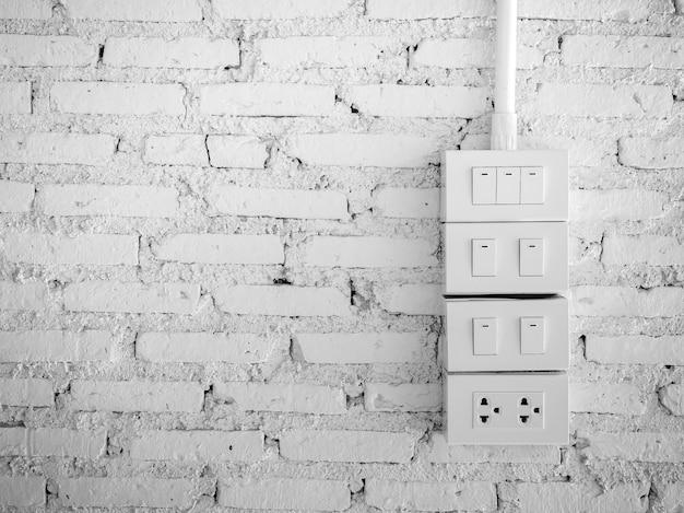Gruppo di interruttore di illuminazione e spina di sbocco, colore bianco sul fondo bianco del muro di mattoni di lerciume.