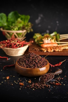 Gruppo di barbecue alla griglia mala (bbq) con pepe di sichuan, cibo di strada caldo e speziato e delizioso su tavola di legno e ingredienti (peperoncino, pepe di sichuan, aglio)