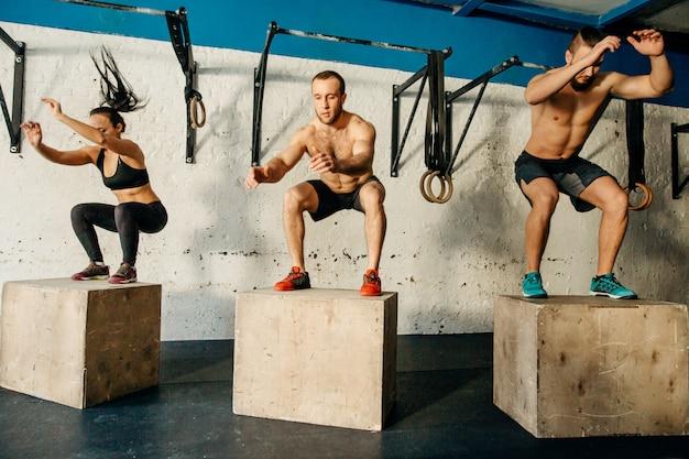 Gruppo di uomo e donna che salta sulla scatola in forma in palestra