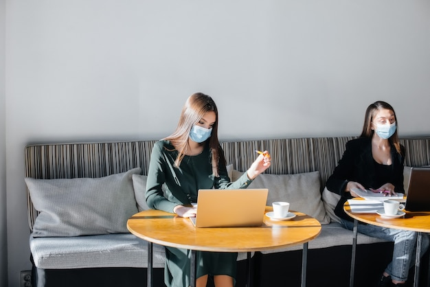 Un gruppo di ragazze mascherate mantiene una distanza sociale in un bar quando lavora al laptop.