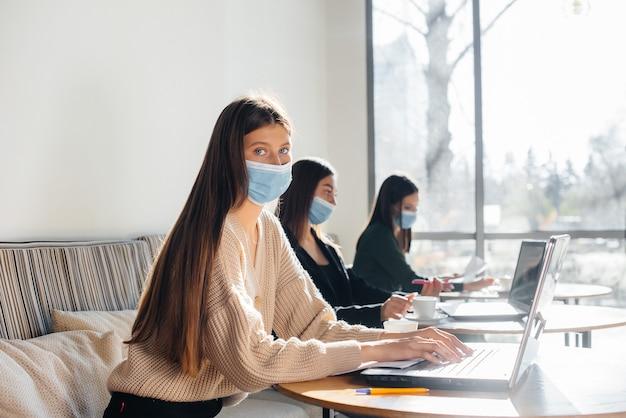 Un gruppo di ragazze mascherate mantiene una distanza sociale in un bar quando lavora sui laptop