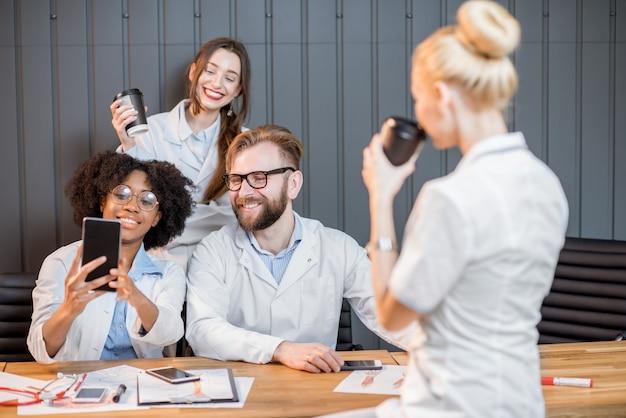 Gruppo di studenti di medicina che si divertono a fotografare con i telefoni durante la pausa caffè in classe