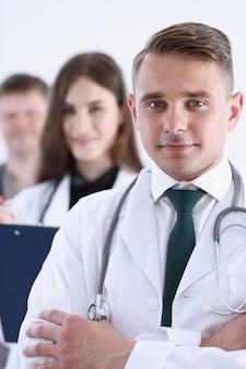 Gruppo di medici con orgoglio in posa in fila e guardando a porte chiuse