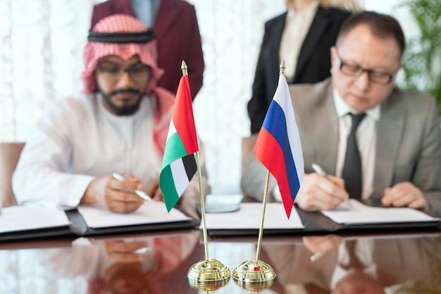 Un gruppo di uomini seduti a un tavolo con bandiere e che firmano un accordo o un contratto