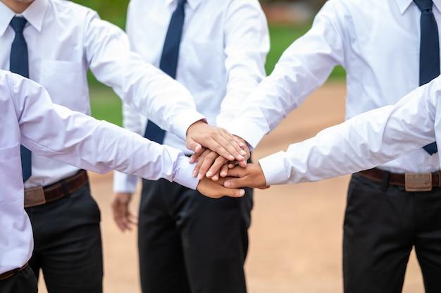Un gruppo di uomini che indossano camicie bianche in piedi in stretta di mano all'aperto