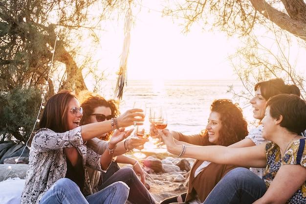 Gruppo di giovani donne adulte di mezza età che si divertono insieme brindando e tintinnando con bicchieri di vino in spiaggia durante un tramonto dorato godendo attività di svago all'aperto o vacanze