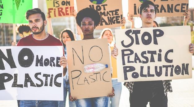 Gruppo di manifestanti millenari su strada, giovani di diverse culture e razze combattono per l'inquinamento da plastica e i cambiamenti climatici - concetto di riscaldamento globale e ambiente - focus sui volti