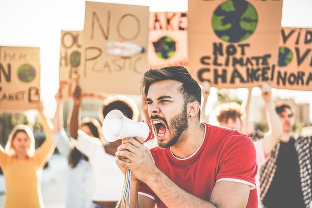 Gruppo di manifestanti millenari su strada, giovani di diverse culture e razze combattono per l'inquinamento da plastica e i cambiamenti climatici - concetto di riscaldamento globale e ambiente - focus sul volto dell'uomo