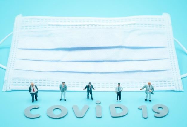 Un gruppo di uomini d'affari in miniatura si trova di fronte al globo terrestre per negoziare la cooperazione commerciale internazionale, durante la crisi covid-19. affari, economia, concetto di assistenza sanitaria