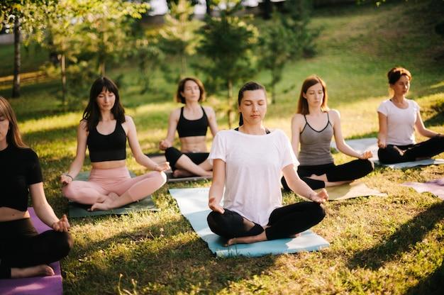 Un gruppo di donne di età mista sta praticando yoga e meditando la mattina nel parco cittadino durante l'alba. un gruppo di persone è seduto all'aperto nella posa del loto sull'erba con gli occhi chiusi