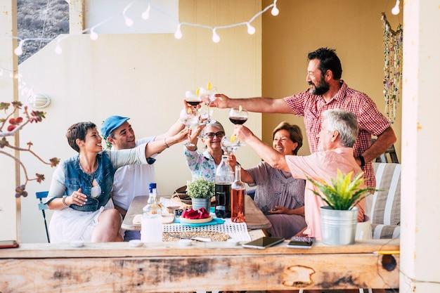 Gruppo di amici di età e generazioni miste, la famiglia si diverte insieme a fare tintinnare e brindare durante l'ora di pranzo con cibo e bevande