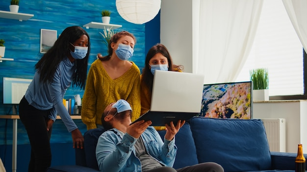 Gruppo di amici di razza mista che si divertono a mantenere le distanze sociali con la maschera facciale che impedisce la diffusione del coronavirus guardando il video sul laptop. in soggiorno a bere birra e mangiare patatine.