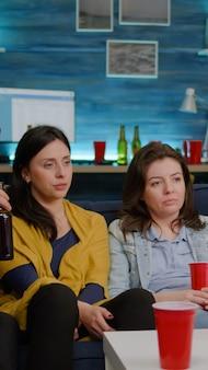 Gruppo di amici di razza mista che si rilassano sul divano mentre guardano film di intrattenimento in televisione che ridono fino a tardi in soggiorno durante la festa in casa. gruppo di persone multietniche che si divertono insieme