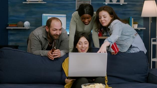 Gruppo di persone di razza mista che trascorrono del tempo insieme a guardare film comici