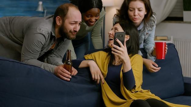 Gruppo di persone di razza mista che trascorrono del tempo insieme mentre guardano un video comico