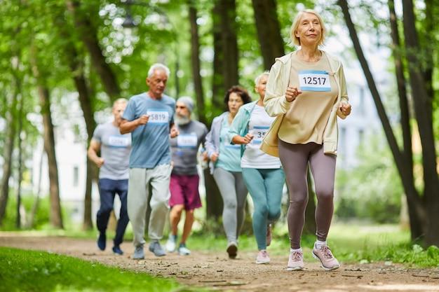 Gruppo di uomini e donne senior attivi moderni che trascorrono il giorno insieme nel parco in esecuzione la maratona, campo lungo