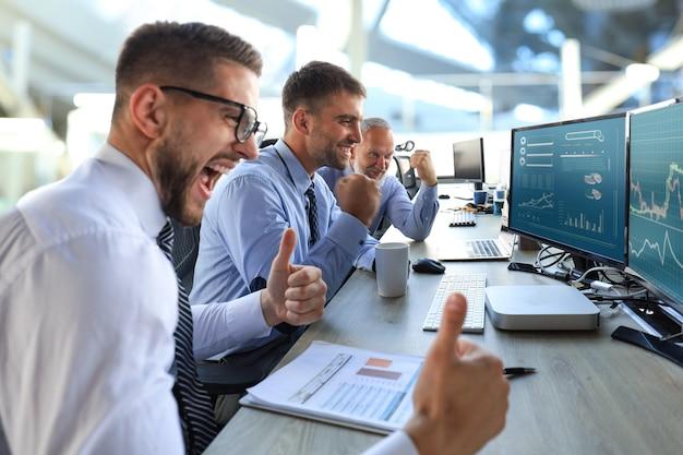 Gruppo di uomini d'affari moderni in abiti da cerimonia che sorridono e gesticolano mentre lavorano in ufficio.