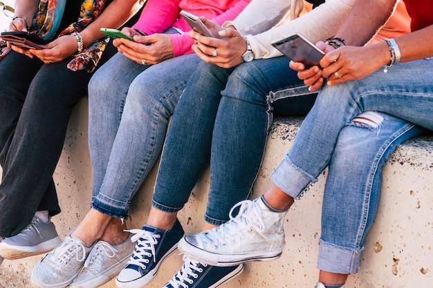 Gruppo di donna moderna casual irriconoscibile seduta sul muro che utilizza dispositivi telefonici moderni per social network e media internet - amicizia in modo moderno e millenario