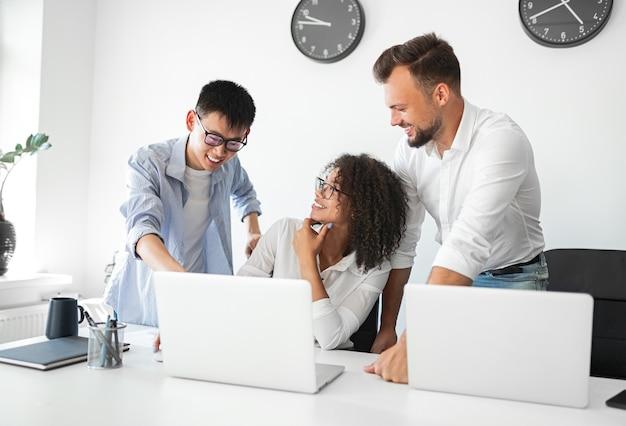 Gruppo di colleghi multirazziali creativi moderni che utilizzano laptop e condividono idee mentre discutono del progetto di business in un ufficio leggero contemporaneo