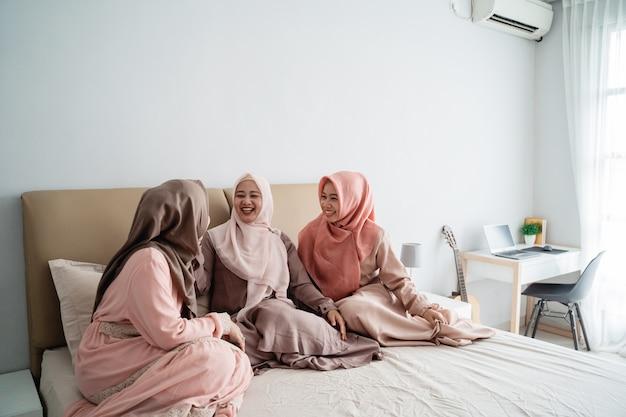 Il gruppo di donna musulmana che si siede sul letto gode di di chiacchierare insieme