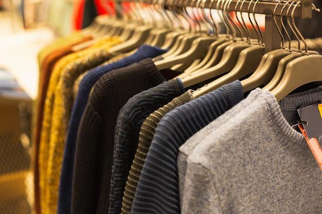 Gruppo di maglioni multicolori appesi trempels in una boutique di moda in vendita
