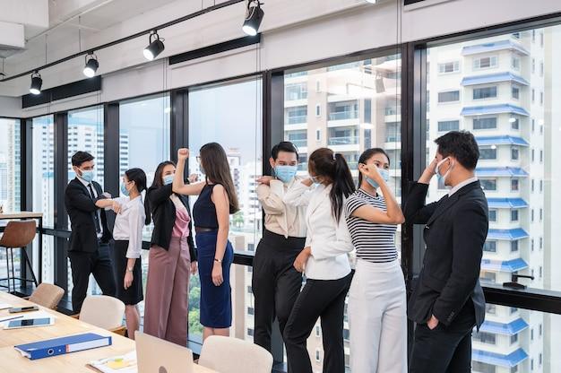 Gruppo di multietnico collega di lavoro che indossa la maschera per il viso saluto con il gomito nel nuovo ufficio normale